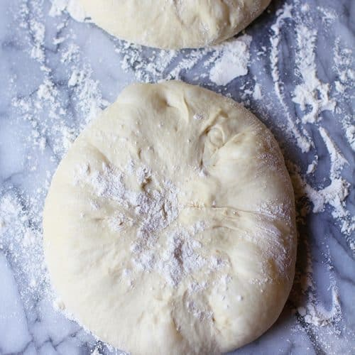 Overhead shot of two mounds of homemade pizza dough, with flour sprinkled on top.