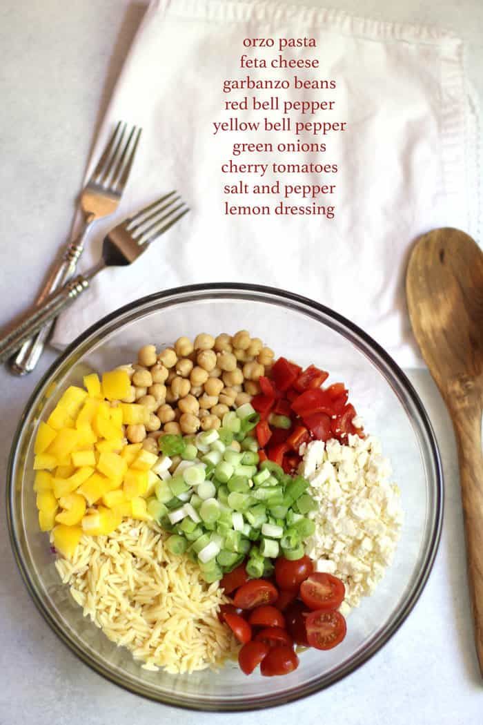 Overhead shot of a glass bowl of orzo pasta salad ingredients, with the ingredient list on a napkin.