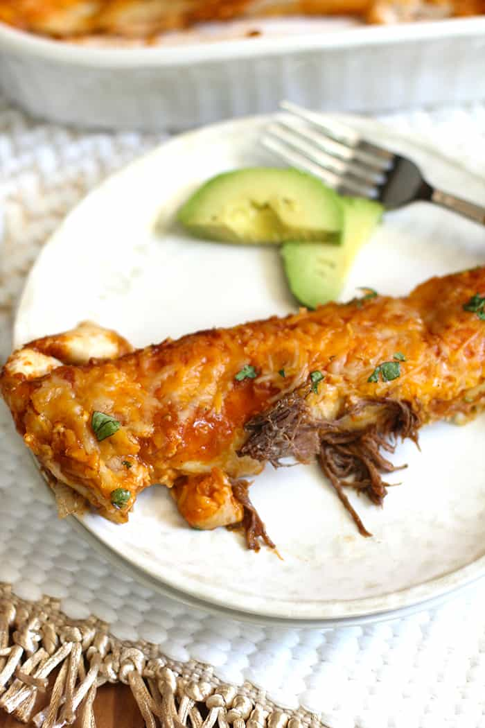 One shredded beef enchilada on a serving plate with sliced avocado and a fork.