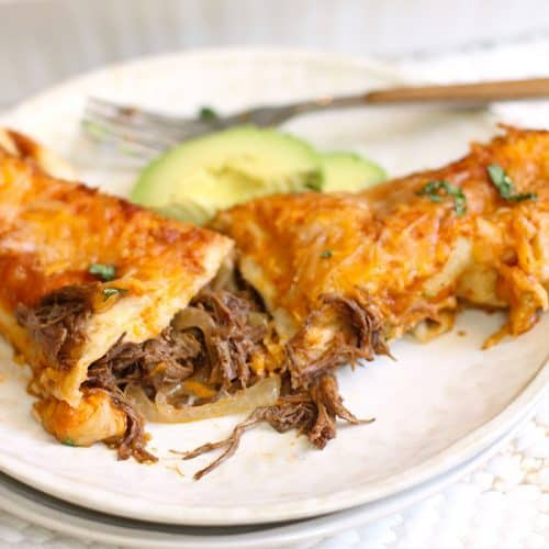 A serving plate with one shredded beef enchilada cut in half, with the casserole in the background.