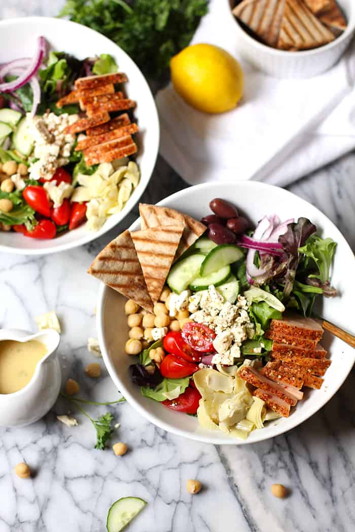 Overhead shot of two bowls of traditional Greek salads with smoked turkey breast.
