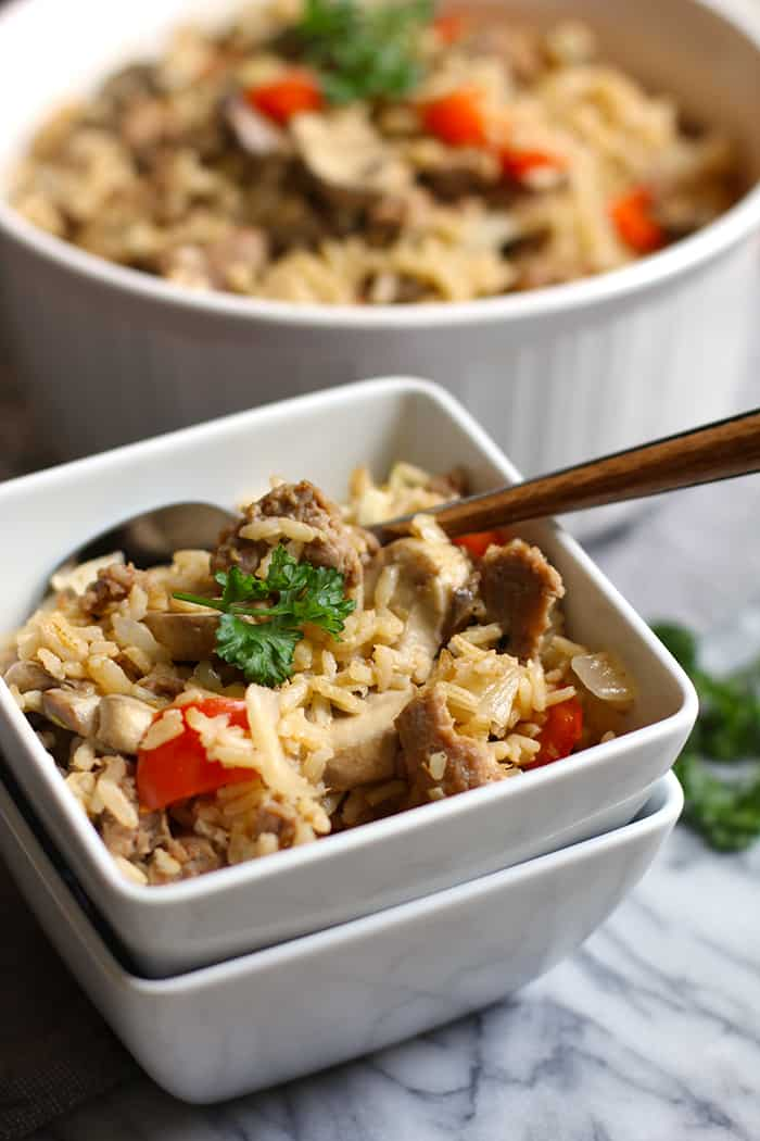 Side shot of a square serving bowl of turkey sausage brown rice, with a fork inside.