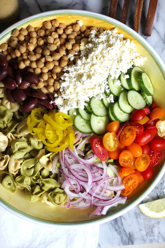 A large bowl of tortellini pasta salad ingredients, separated by ingredient.