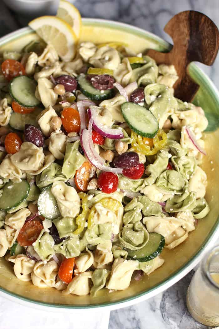 Greek Tortellini Pasta Salad combines cheese-filled tortellini with garbanzo beans, feta cheese, olives, lots of veggies, and a fresh greek vinaigrette!   suebeehomemaker.com