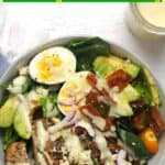 A serving bowl of grilled chicken Cobb Salad with honey mustard drizzled on top.