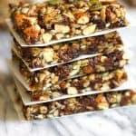 Side shot of a stack of trail mix granola bars, on a white and gray background.