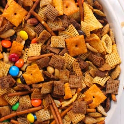 Overhead shot of a partial bowl of spicy Chex party mix, in a white shallow bowl with handles.