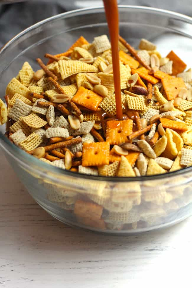 Side shot of the seasoning mix being drizzled in the middle of the Chex party mix.
