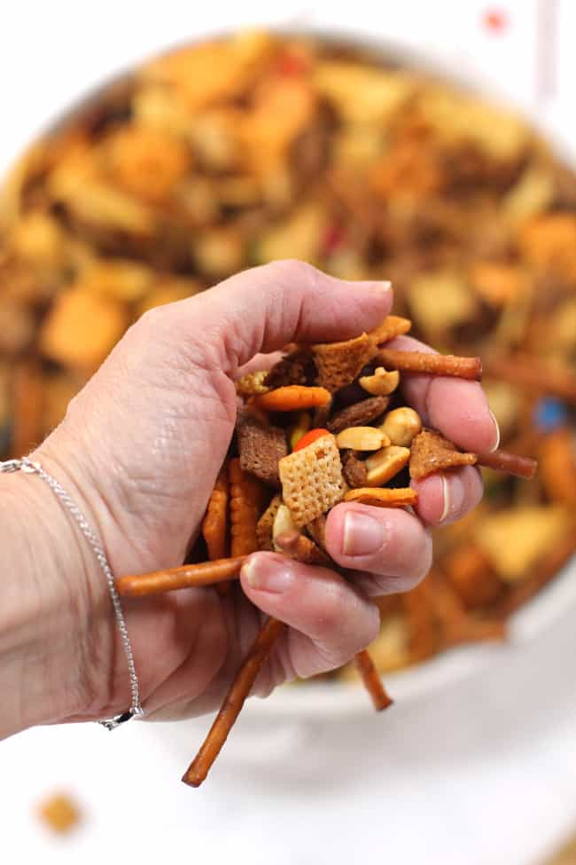 Overhead shot of a handful of spicy Chex party mix, over a large bowl of party mix.