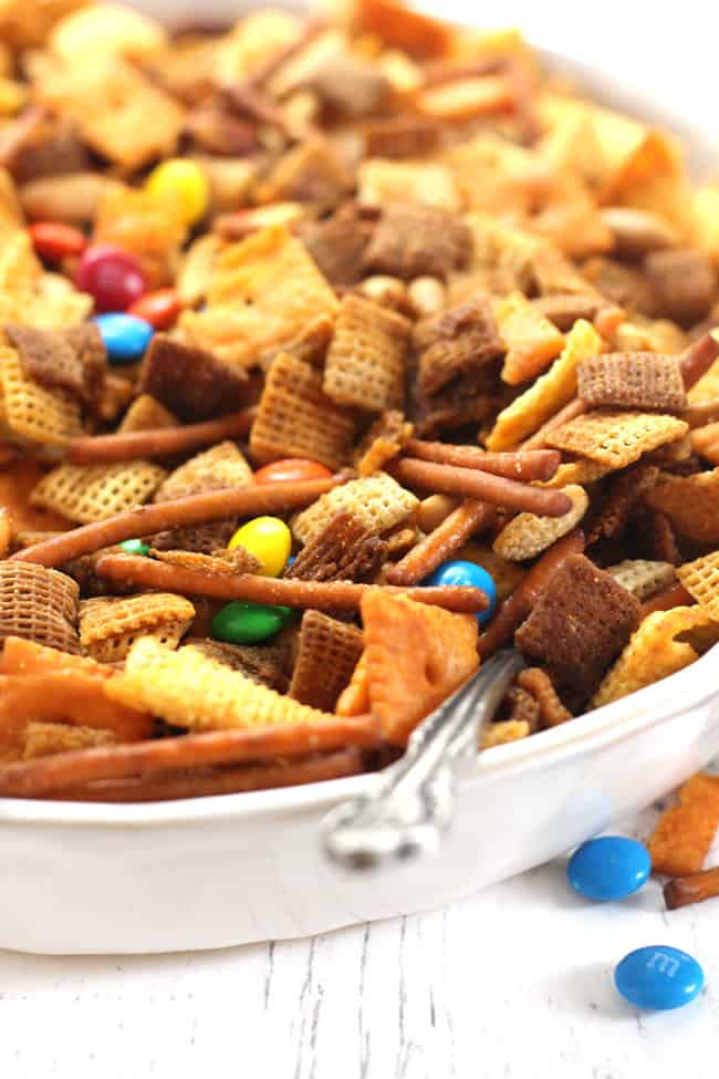 Side shot of a white bowl of spicy Chex party mix.