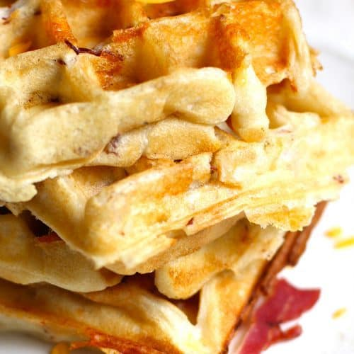 Bacon Cheddar Waffles combine a buttermilk waffle with bacon and cheddar mix-ins, topped with an egg cooked over-easy, and a big drizzle of maple syrup! | suebeehomemaker.com