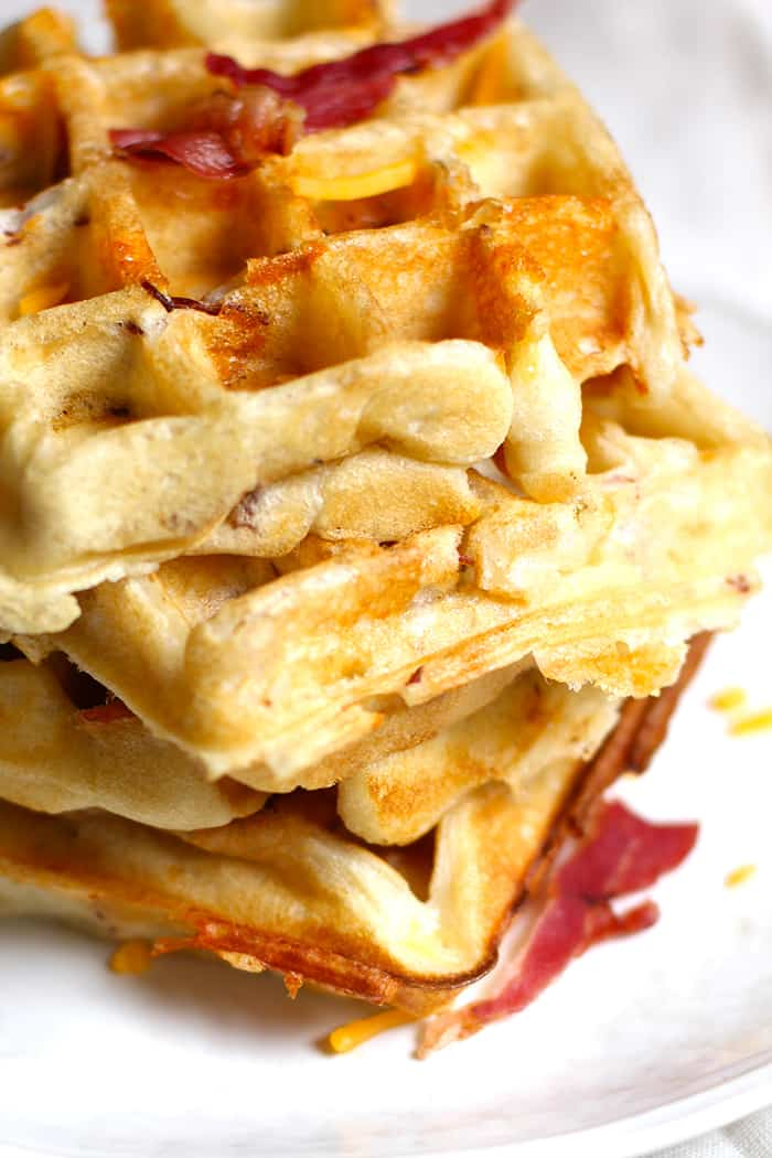 A close up of a stack of bacon cheddar waffles.