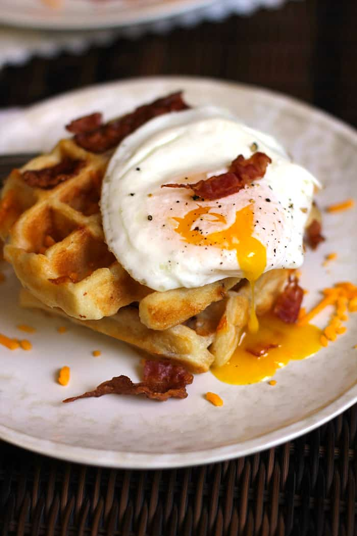 Bacon Cheddar Waffles combine a buttermilk waffle with bacon and cheddar mix-ins, topped with an egg cooked over-easy, and a big drizzle of maple syrup!   suebeehomemaker.com