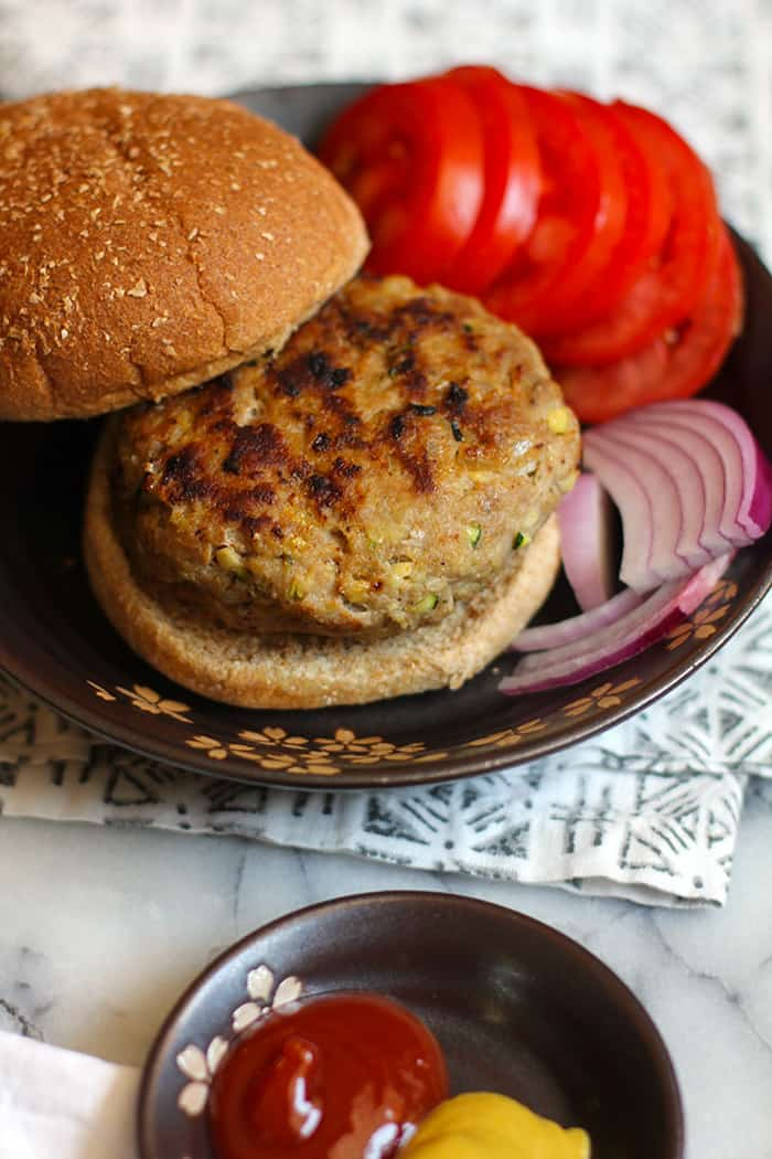A grilled zucchini turkey burger on a bun, with tomatoes and onions.