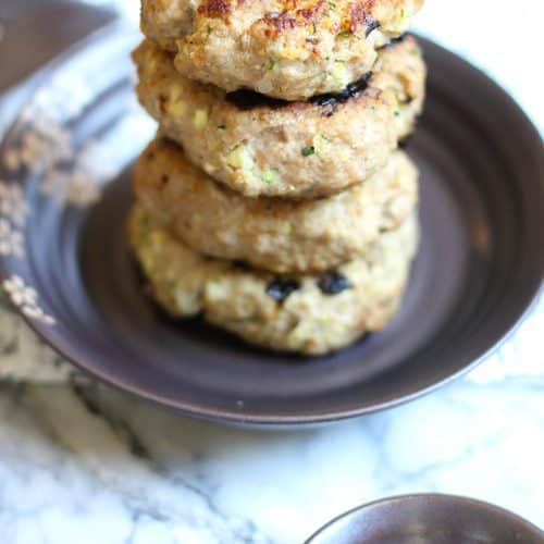 A stack of four grilled zucchini turkey burgers on a plate.