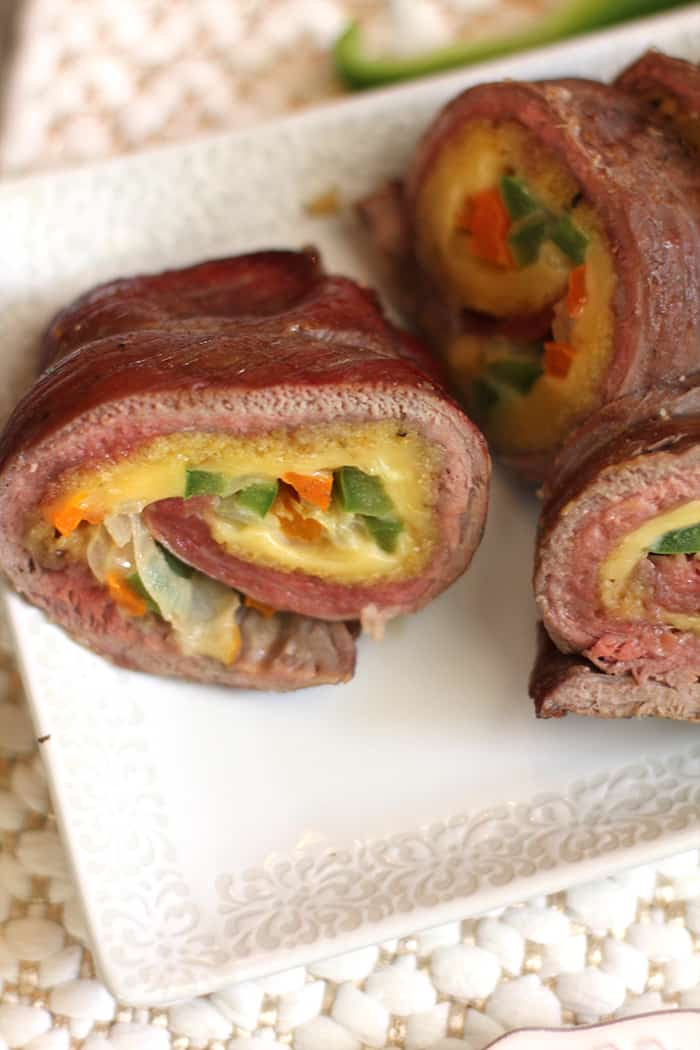 Stuffed Flank Steak Roll combines a tender cut of beef, with a bread crumb mixture, smoked gouda cheese, and a pepper and onion sauté - rolled and grilled! | suebeehomemaker.com