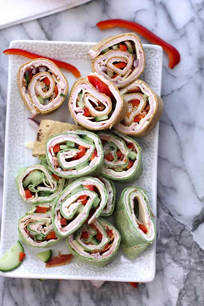 Make school lunches fun again with these Turkey Club Roll-Ups. Simply layer any wrap with veggie cream cheese, turkey, bacon, cheese, and veggies! | suebeehomemaker.com