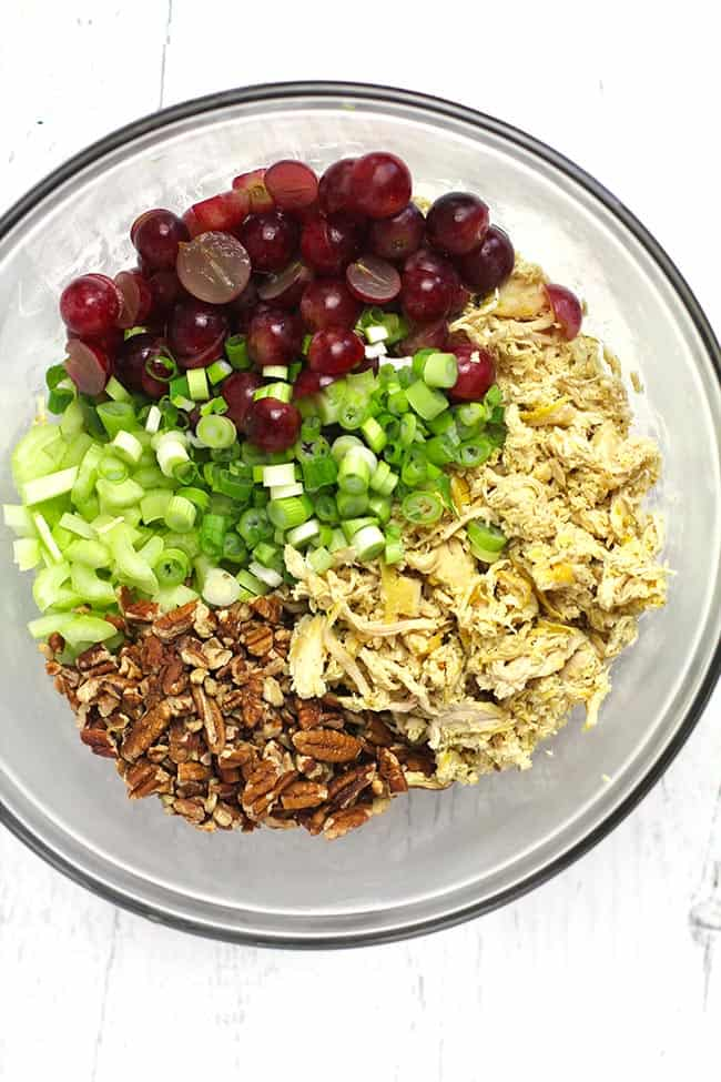 Overhead shot of a clear bowl containing all the chicken salad ingredients divided by ingredient.
