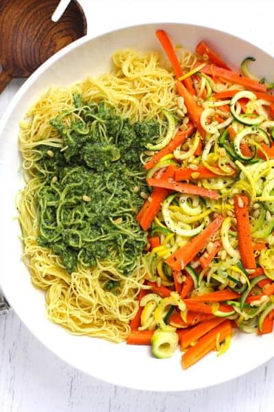 Overhead shot of a large white bowl of pesto vegetable pasta, on a white background.