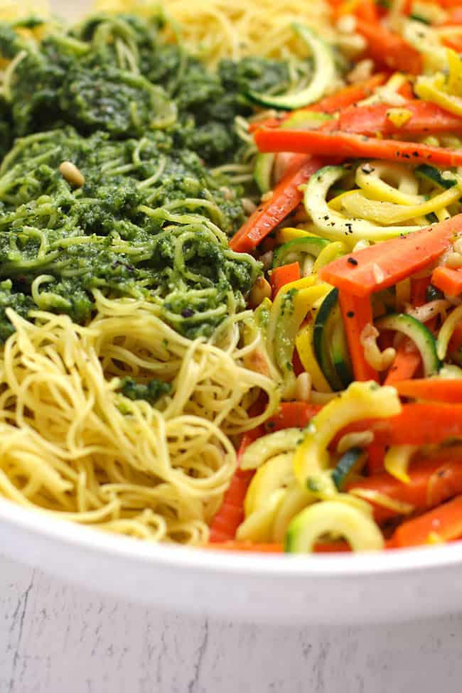 Side shot of a large white bowl filled with spiraled veggies and angle hair pasta topped with pesto sauce.