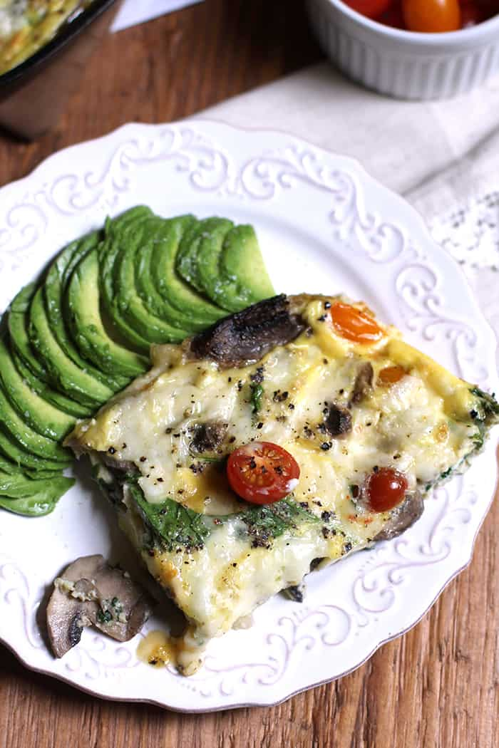 A white plate with a pice of creamy vegetable frittata, with sliced avocado.