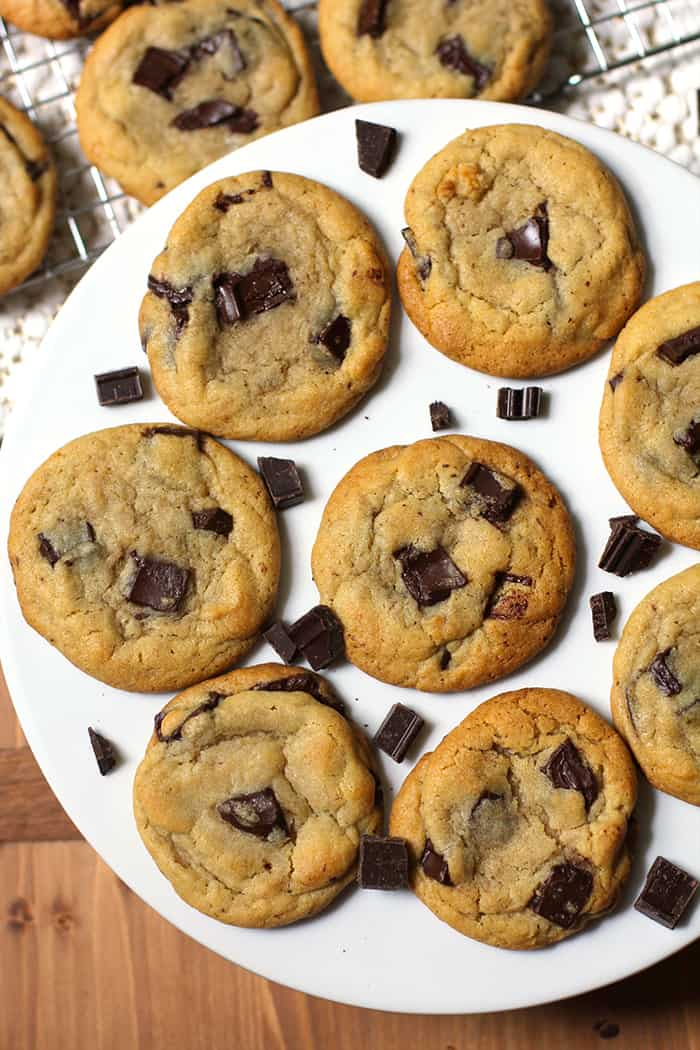 A round cake white plate full of dark chocolate chunk cookies.
