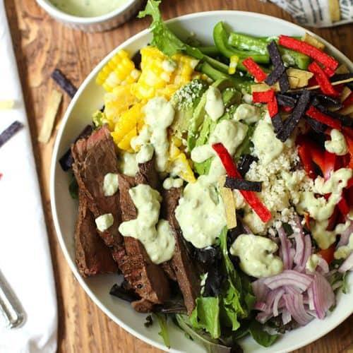 Overhead shot of a flank steak fajita salad with creamy avocado dressing drizzled on top.