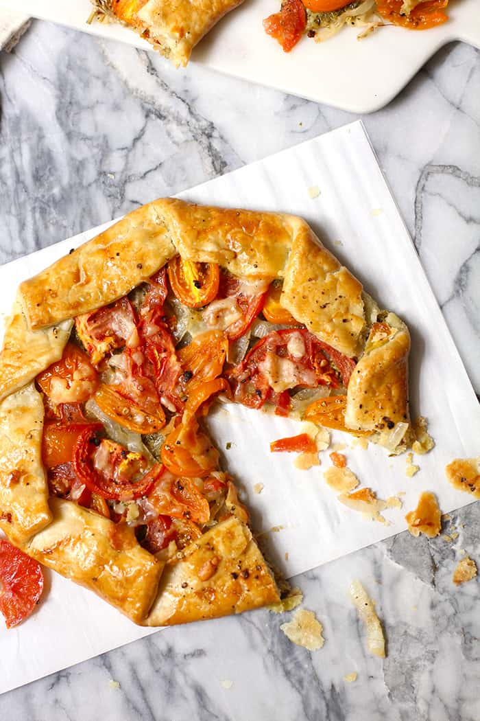 My Savory Italian Galette uses a store-bought pie crust, pesto sauce, sautéed onions, fresh tomatoes, and shaved parmesan cheese to create an amazing dish! | suebeehomemaker.com