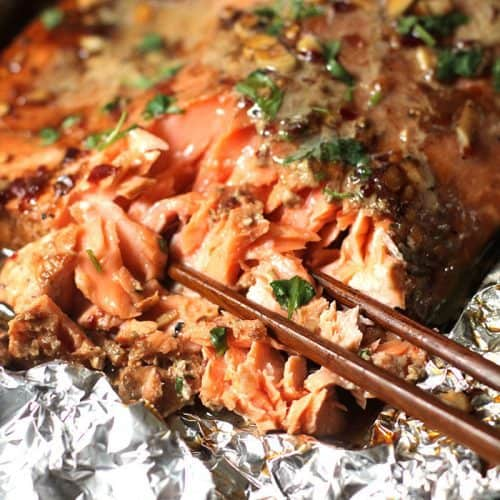 A large filet of cooked Asian salmon, on foil, with chopsticks pulling some apart.