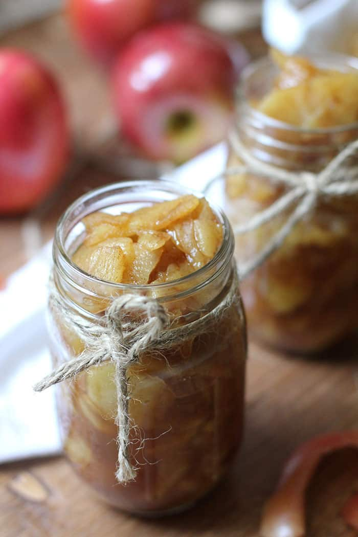A mason jar with brown twine tied on it, full of homemade applesauce, on a brown background with bright red apples in the background and another jar of applesauce.