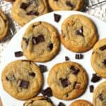 A round white plate full of dark chocolate chunk cookies.