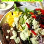Closeup on a flank steak fajita salad with creamy avocado dressing drizzled on top.