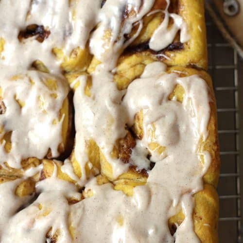 Close-up shot of pumpkin cinnamon rolls with icing on top, all on a wire rack.