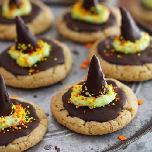 Side angle of a gray cake platter with witch hat peanut butter cookies on top, with a halloween decoration in the background and more cookies.
