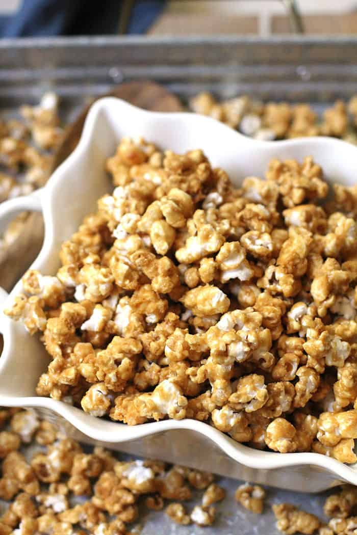 Overhead shot of caramel popcorn in a square white bowl, on a gray tray with popcorn in it as well.