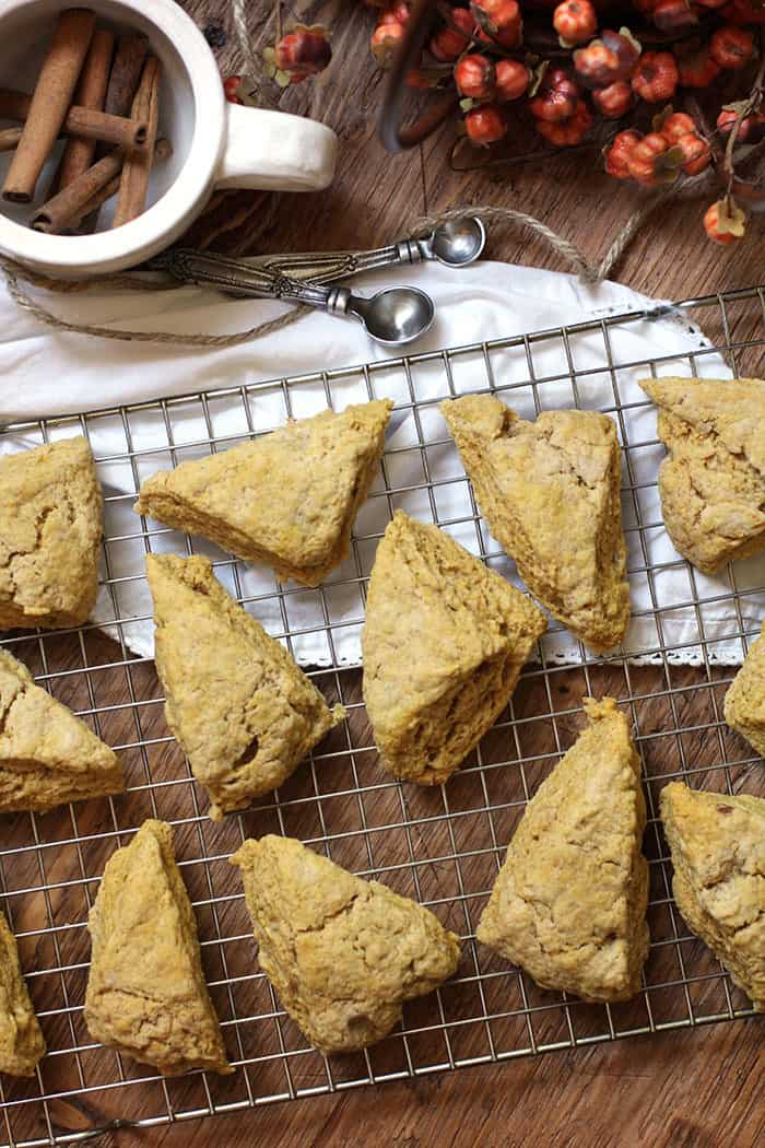 Overhead shot of unglazed pumpkin scones on a wire rack, over a wooden background, with a white napkin, cinnamon sticks, and a pumpkin decoration in the background.