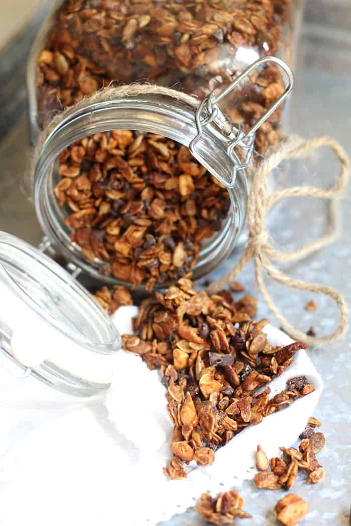 Side shot of a extra large jar tipped on it's side, with granola spilling out, on a gray tray.