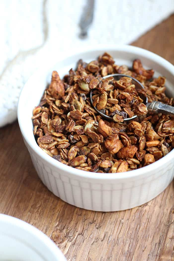 Side shot of a small round white bowl, with granola in it, and a measuring spoon inside it.