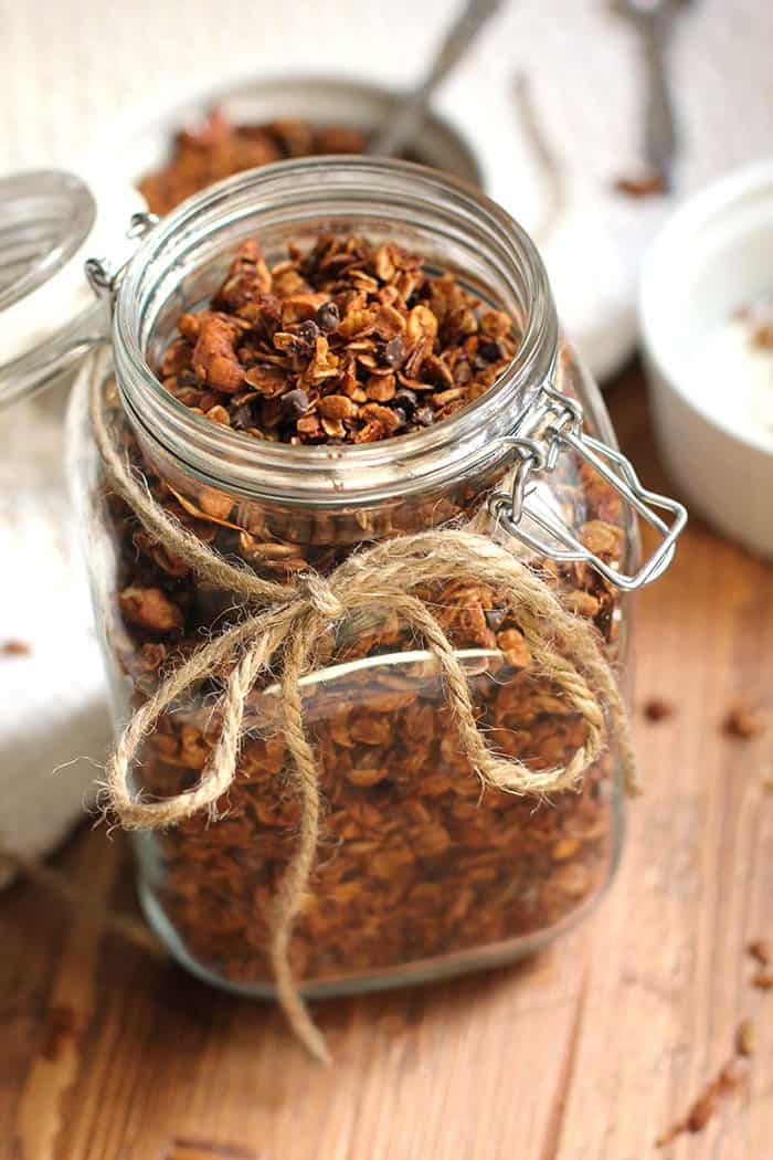 Side shot of a extra large jar filled with granola, with twine around the top, on a wooden background.