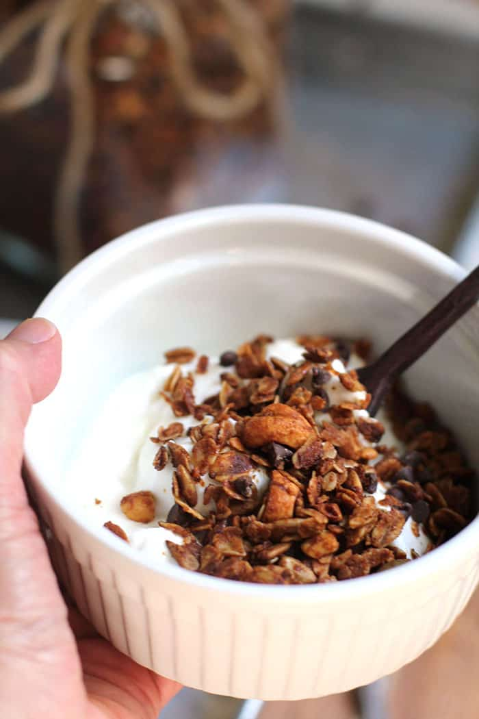 Close-up shot of my hand holding white bowl, with yogurt and granola on top.