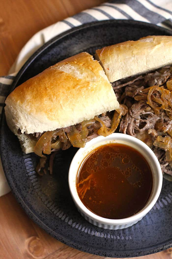 Overhead shot of a beef au jus sandwich, sliced in half, on a black plate with a small white bowl of au jus.