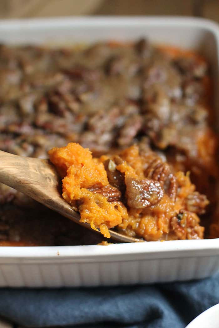 A side view of a white casserole dish of sweet potato casserole, and a wooden spoon lifting some up, with the background out of focus.
