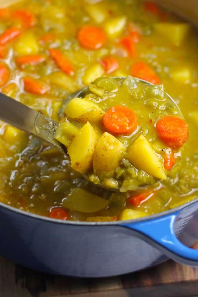 Overhead shot of a soup ladle of spit pea vegetable soup, over a blue pot.