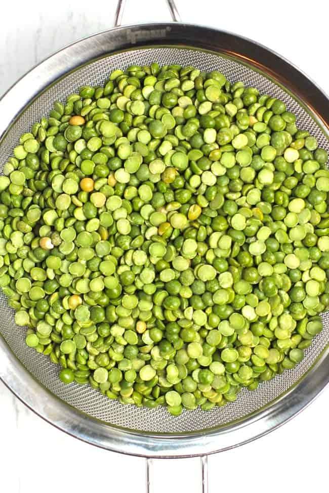 Overhead shot of a strainer of uncooked split peas.