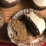 Overhead shot of three gingerbread muffins with icing, and one muffin cut open so you can see how moist it is, all on a wooden background with a red placemat.