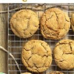 Six gingersnap cookies on a cooling rack, on a wooden board.