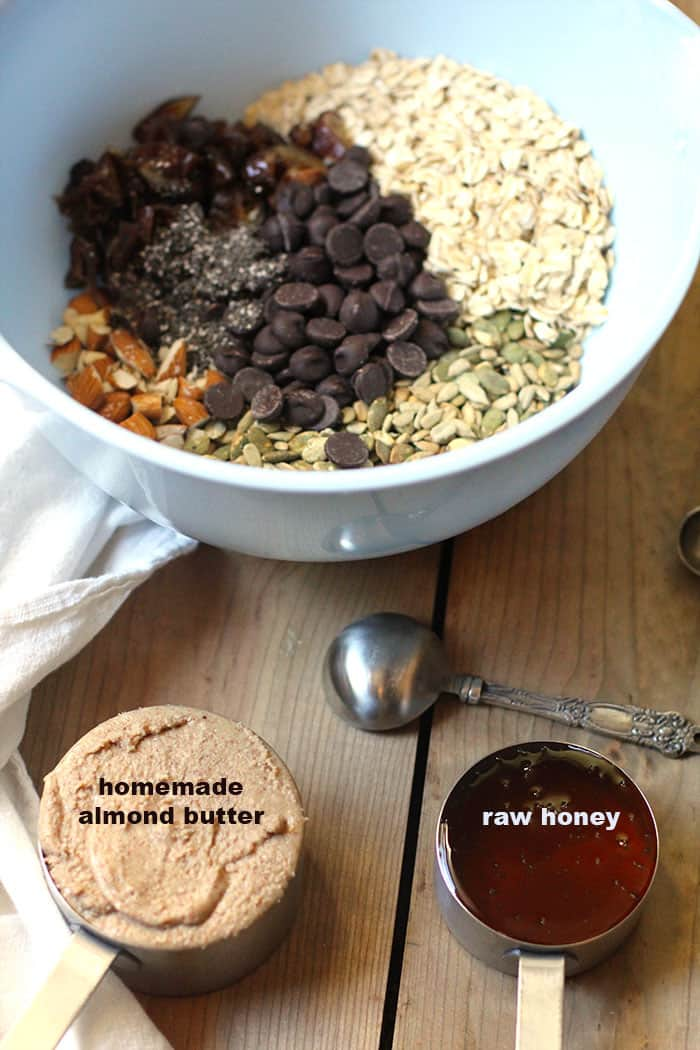 A blue mixing bowl full of energy bite ingredients, with a measuring cup of homemade almond butter and one of raw honey.