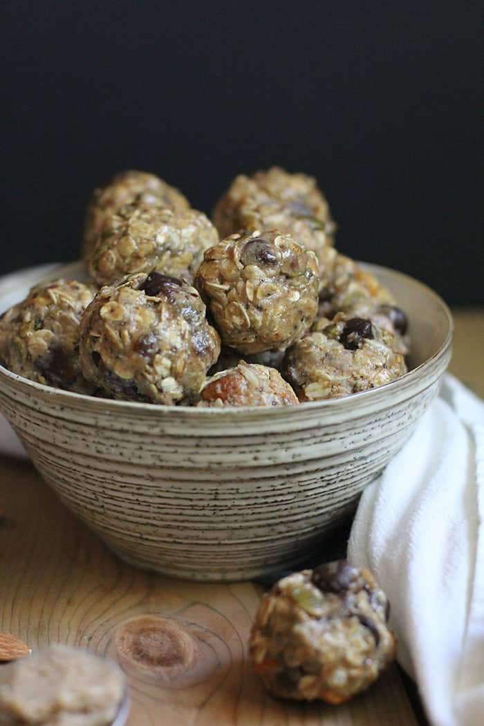 A side shot of a bowl of almond butter energy bites, on a wooden background with a white towel.