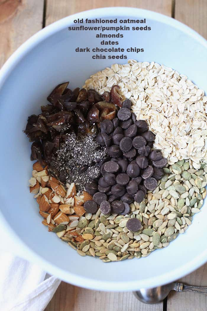 Overhead shot of blue mixing bowl full of energy bite ingredients, separated by ingredient.