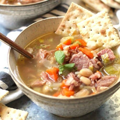 Two bowls of leftover ham and white bean soup, with saltine crackers.